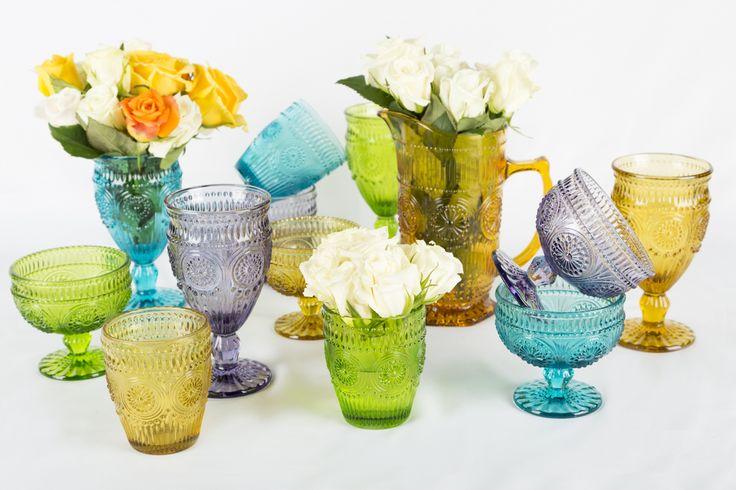Los vasos y las copas de colores son ideales para decorar la mesa en una ocasión especial. Usa flores, velas o piedras de colores.