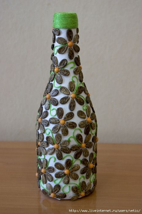 a bottle decorated with water melon's seeds. very smart and beautiful.