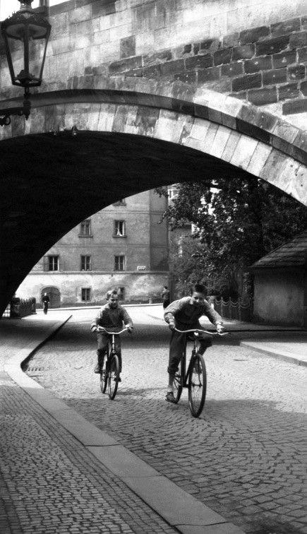 Kluci na kolech (637-4) • Praha, červen 1960 • | černobílá fotografie, Kampa, oblouk Karlova mostu, dlažba, lucerna  |•|black and white photograph, Prague|