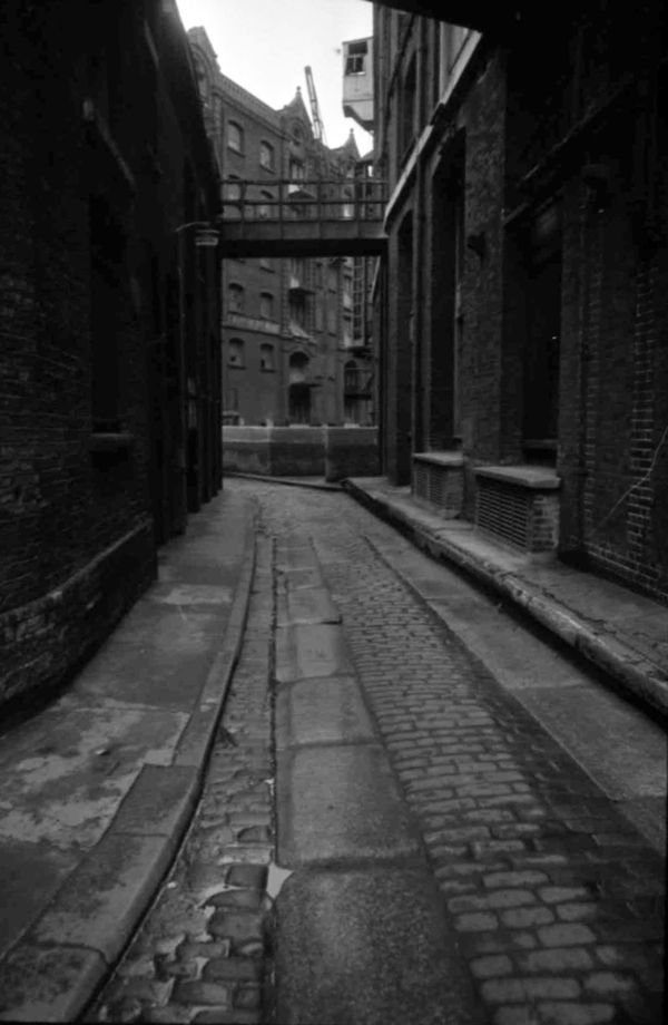 There is little traffic on the road, children are at play, housewives linger in doorways, old men doze outside the library and, in the distance, a rag and bone man's cart clatters down the street. This is the East End in the afternoon, as photographed by newspaper artist Tony Hall in the nineteen sixties while wandering with his camera in the quiet hours between shifts on The Evening News in Fleet St.
