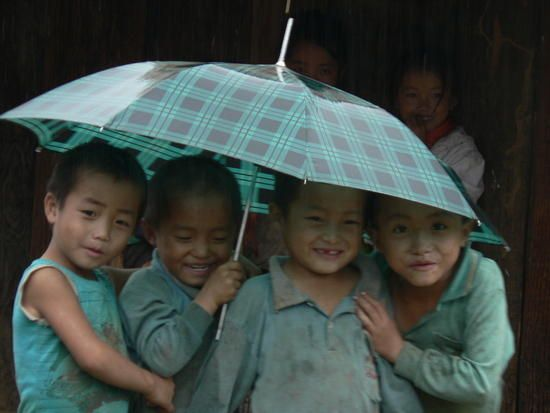 "Hmong (pronounced ""mung"",a people who live in southeast Asia) children playing in the rain!"