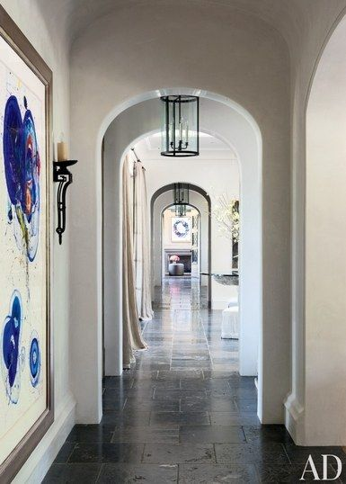 A large artwork by Sam Francis hangs in the hallway of Gisele Bündchen and Tom Brady's Los Angeles home, which is paved in antique Belgian bluestone; the Joan Behnke–designed lanterns and the sconce are by Paul Ferrante | archdigest.com