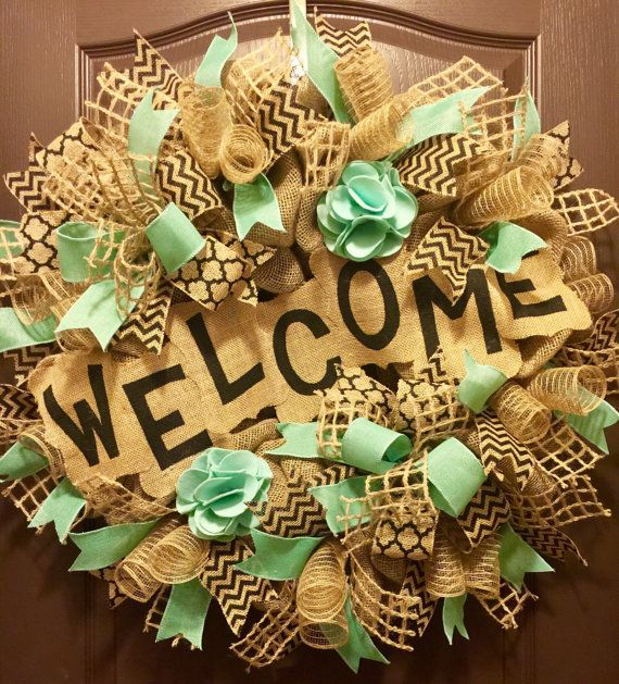 This is an XL Wreath measuring 31 in diameter. It is made on a wire wreath frame from burlap, light teal burlap wired ribbon, jute wired ribbon, black chevron burlap wired ribbon & black keyhole burlap wired ribbon. It is adorned with 2 large handmade felt flowers and a large hand painted welcome banner in the center. This wreath can be perfectly displayed year round and is READY TO SHIP to a loving home.