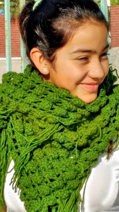 Shawl verde a crochet utilizado como bufanda.