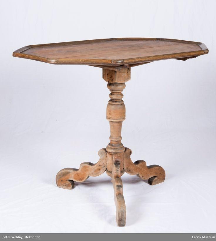 8-kantet plate med list festet med trenaglerplaten kan vippes opp. Bordplaten festet til en dreiet og høvlet søyle, tre svugne, sveifede ben med rektangulært horisontalsnitt