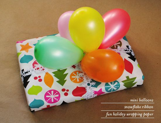 use mini balloons as a present topper. i used snowflake ribbon & seasonal wrapping paper for a holiday version! photo by Oh Joy.