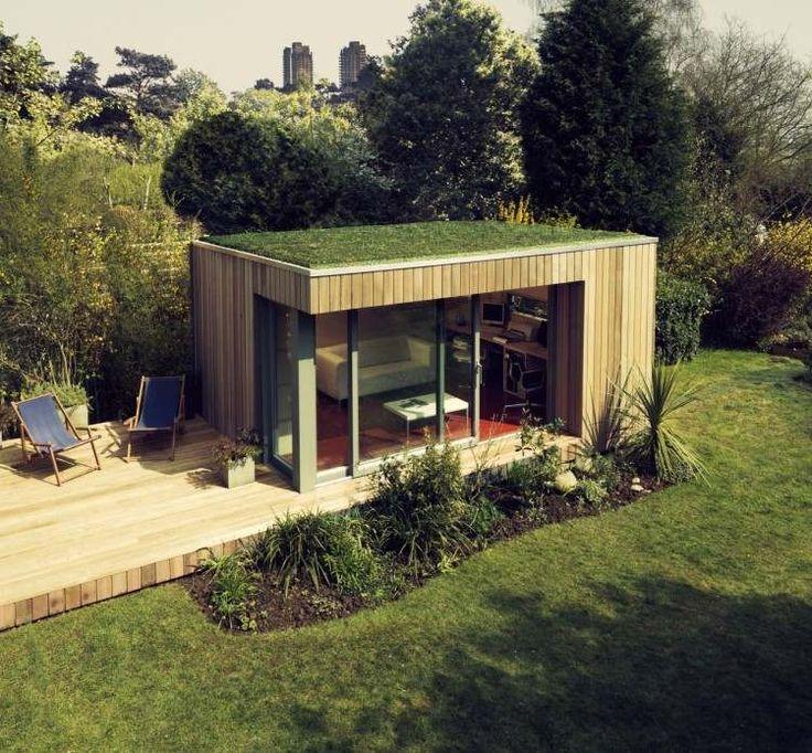 abri de jardin éco avec toit recouvert de gazon, petite terrasse en bois et deux chaises de jardin