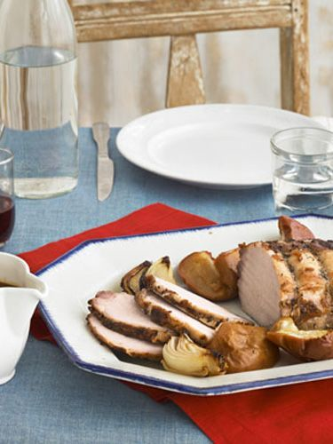 Cider-Brined Pork Roast with Onions and Apples: An apple cider brine keeps this roasted pork moist and full of flavor. - CountryLiving.com