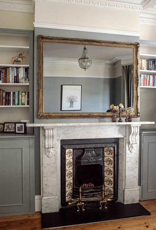 Victorian fireplace with huge mirror to fill wall space. The marble surroundings match the neutral blue walls