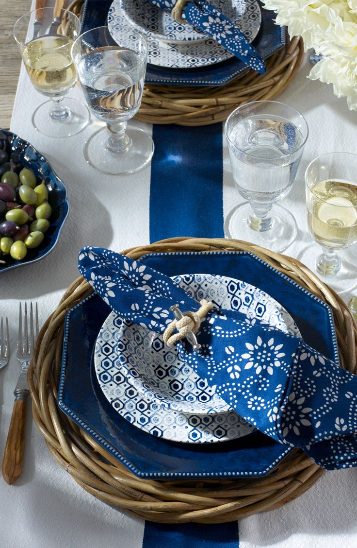 A summer table in the spirit of the French Riviera mixes blue and white patterns atop the rustic, hand-woven Pernay charger. A perfect setting for outdoor dining.