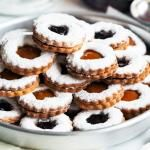 I can't image celebrating Christmas without these brittle linzer cookies, filled with our favorite marmalade. They look incredibly beautiful, but they taste even better. Brittle, sweet and delicious. You can use your favorite marmalade, however we usually use the one we made early in the year. This year we filled them with apricot and grape marmalade and they are beyond delicious. You can never go wrong with a classic + you can store these for up to 10 days in a tightly closed box, how great…