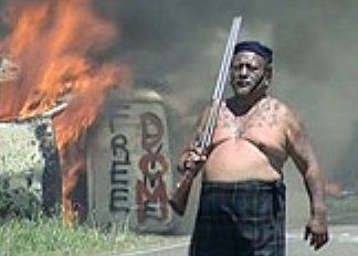 """On 16 January 2005 during a powhiri (greeting ceremony) which formed part of a Waitangi Tribunal hearing, Iti fired a shotgun into a New Zealand flag in close proximity to a large number of people, which he explained was an attempt to recreate the 1860s East Cape War: """"We wanted them to feel the heat and smoke, and Tūhoe outrage and disgust at the way we have been treated for 200 years.""""[12] The incident was filmed by television crews but initially ignored by police"""