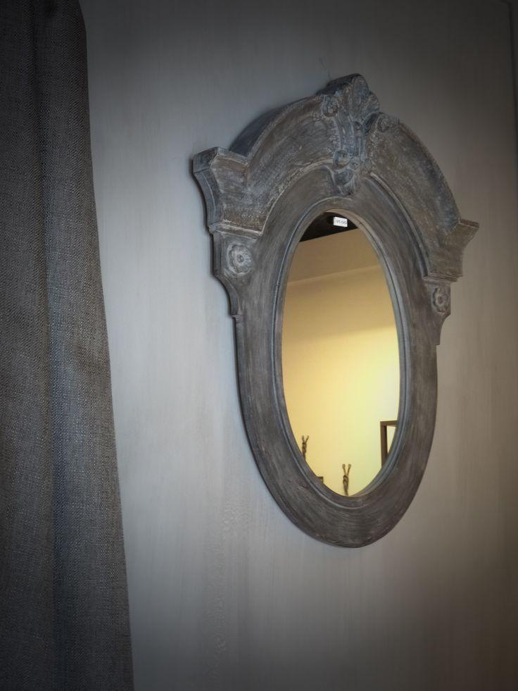 Ossenoog houten spiegel met een stoeren linnen lap stof tegen een beton look geschilderde muur brengt een warme gloed in uw woonkamer.