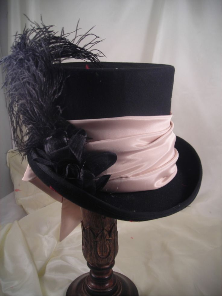 Elegant top hat, soft contrasting fabric, and feathers. I like the large fabric band that mimics the draping of a lot of Victorian dresses.