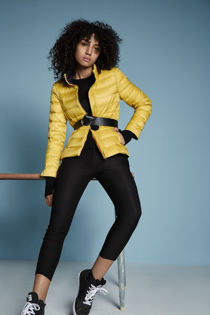Get the trend right by wearing a puffer jacket tied up with belt.  Athleisure, sports luxe, yellow jackets, yellow puffer jacket, black tights with yellow puffers jackets, lace up sneakers, puffer jackets with belt.