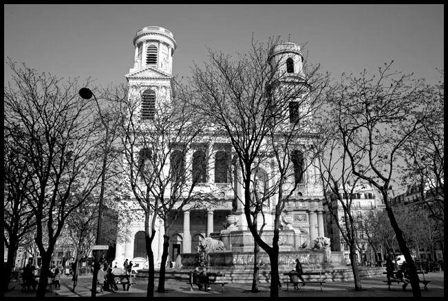 """E' il 19 ottobre 1974, ore 12,30. Georges Perec è seduto su una panchina """"in mezzo ai piccioni"""" di place Saint-Sulpice, Parigi.  Da due giorni è impegnato nel suo """"tentativo di esaurimento di un luogo parigino"""", annotando tutto """"quello che non ha importanza"""". Come per esempio i riti di pulizia dei piccioni, le persone che escono dalla chiesa, il sole coperto per un istante da una nuvola. Nessun posto è migliore di una panchina per osservare la vita ordinaria che scorre intorno a noi."""