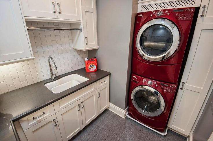 Stacking a red washer and dryer in this gray and white laundry room creates a focal point and saves space in the small area. Vertically stacked subway tile creates a fresh and unexpected backsplash.