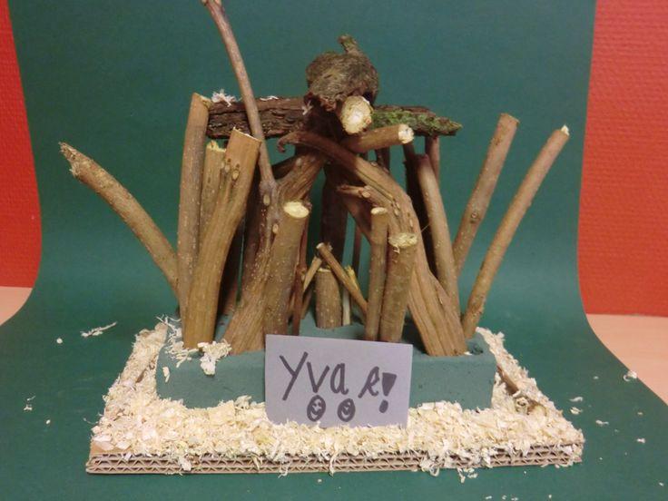 Prehistorisch huis maken. Stokken en schors verzamelen, in de oase steken en afwerken met houtsnippers.