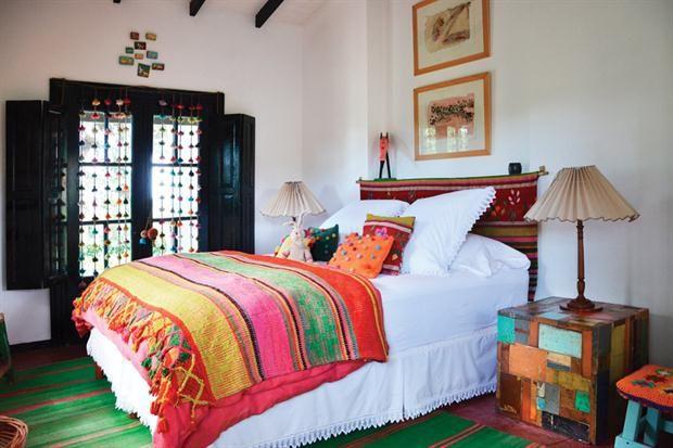 Los tirantes, las carpinterías y los postigones de madera pintada de negro se recortan del fondo blanco dándole profundidad al dormitorio..