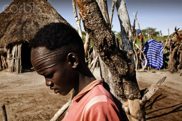 Africa | A young boy, from the Nuer tribe, is seen in a village close to Ayod, Jonglei state, southern Sudan. Nuer practice the tradition of scarification across the forehead as a right of passage. Although this tradition is not practiced as much in the larger towns, it is practiced in smaller villages. | © Stefano De Luigi