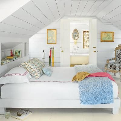 In this upstairs bedroom, built-in shelving provides storage, maximizing the available space under the low, pitched roof. | Coastalliving.com