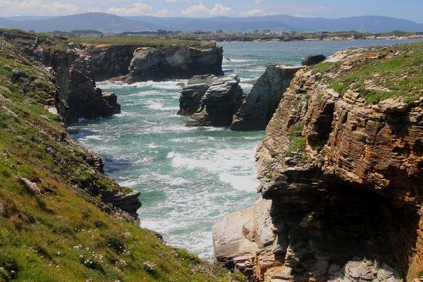 """De Playa de las Catedrals, wat letterlijk """"het strand van de kathedralen"""" betekent, behoort tot de bekendste van Galicië, en werd uitgeroepen tot natuurmonument én een van de mooiste stranden van Europa. De ruige rotsformaties en bogen van leisteen, die soms wel meer dan dertig meter hoog zijn, werden door de wind en de golven van de Atlantische oceaan uitgesleten."""