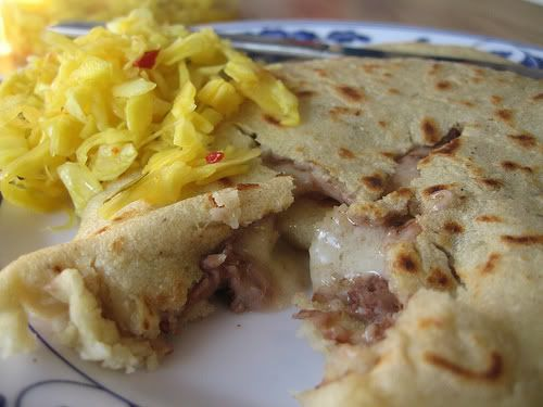 Pupusa salvadorena  -2 Cups of Masa Harina-1 1/2 Cups Water,Salt to taste,1/2 Cup Queso or shredded cheese,1 can refried beans   1.  Combine the masa harina, water and salt in a bowl until the consistency is that of dough.  It should not stick to your hands. 2.In another bowl, mix the refried beans and the cheese until well combined. 3.Take some masa  and form balls 4.Take one ball at a time, poke  a hole with your finger and fill it with the beans + cheese 5. Close the hole flaten and fry