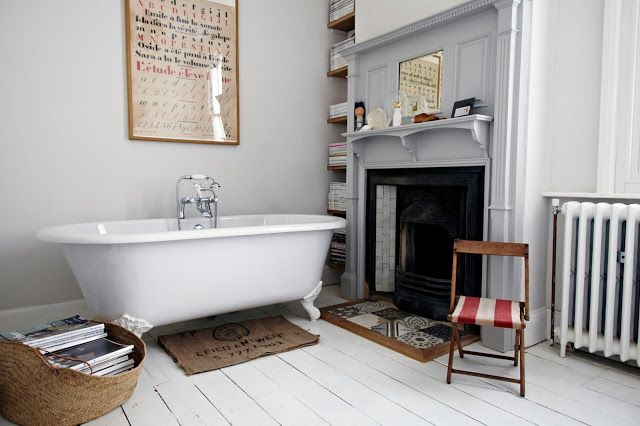 Grey bathroom with roll-top bath, white painted floorboard sand original victorian fireplace. Gorgeous.