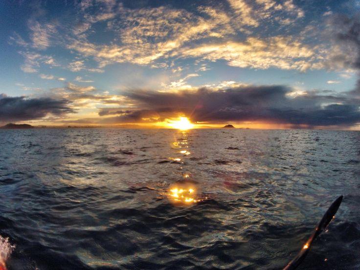 Kayaking as the sun sets over Mauao (Mt Maunganui).  New Zealand.