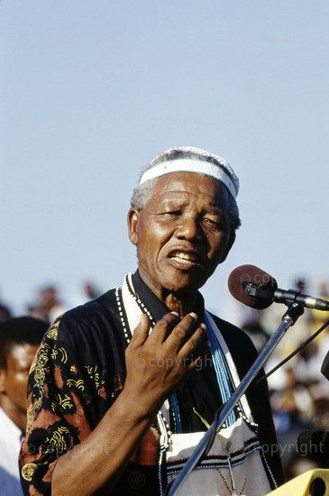 Nelson Mandela addresses a crowd in the former Transkei dressed in traditional Xhosa beads. 1994.
