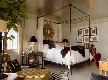 animal furs and a canopy bed offer a stately ambience while a bedside table with a distressed finish displays a modern light fixture