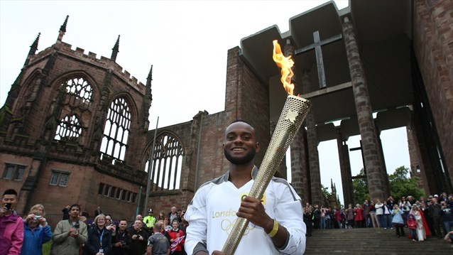 Torchbearer Ali Abdillahi holds the Olympic Flame at the Coventry Cathedral ruins during Day 45 of the London 2012 Olympic Torch Relay.