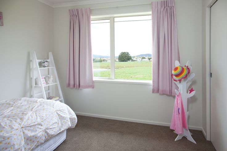 A funky hat and bag stand keeps items off the floor in this young child's bedroom.