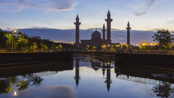 Time lapse of a mosque in Jelutong, Shah Alam, Malaysia during sunrise with reflection. 4K. Motion Timelapse Zoom Out.