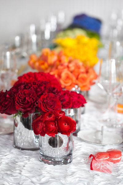 I wouldn't do the rainbow effect but I like this idea of doing bright colored flowers on the tables.