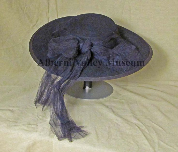 "Large navy blue hat with shallow curved crown and wide gently downward sloping brim, 1946-50. A navy blue grosgrain ribbon and a navy blue net scarf encircle the crown; the net is fashioned into a large bow at the back.  In the late 1940s Christian Dior's ""New Look"" brought about the return of glamorous hats as accessories for the new dress designs.  Hats with shallow crowns and wide brims were the general rule.  [Alberni Valley Museum Collection 1978.22.4]"
