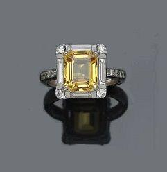 Un anillo de diamante que centran un zafiro amarillo de corte radiante, con un peso aproximado de 3.00 quilates; montado en dieciocho quilates de oro blanco.