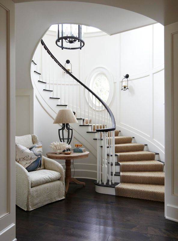This sweeping staircase is gorgeous. A cozy vignette at the foot of the stairs is inviting. - Traditional Home ®/ Photo: Colleen Duffley / Design: Tammy Connor