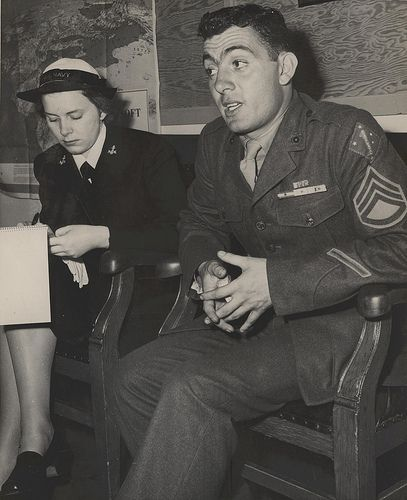"""John Basilone Interviewed by Sigrid Shield, September 1943  """"Marine Congressional Medal of Honor Hero Interviewed. Platoon Sergeant John Basilone, USMC, recently visited the Marine Headquarters at Washington, DC. Pl. Sgt. Basilone's home is Raritan, NJ. He was awarded the Congressional Medal of Honor for """"Extraordinary heroism and conspicuous gallantry in action above and beyond the call of duty."""" Here, he is pictured being interviewed by a Wave, Yeoman 3/c Sigrid Shield."""""""