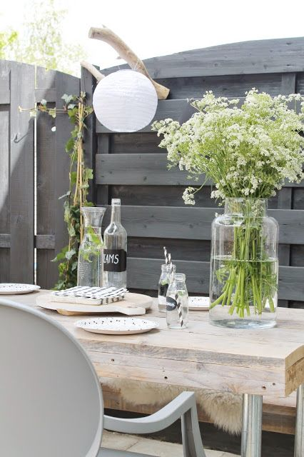nice outside space wooden table designer chair greenery grey walls