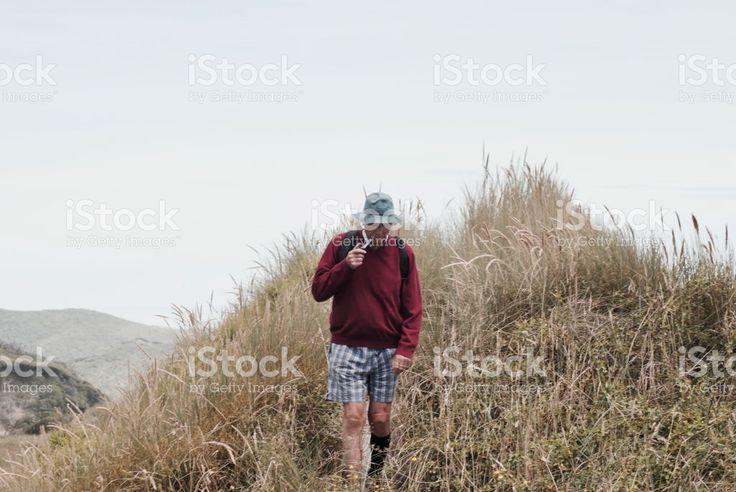 A Senior Man Smokes his Pipe whilst Walking royalty-free stock photo