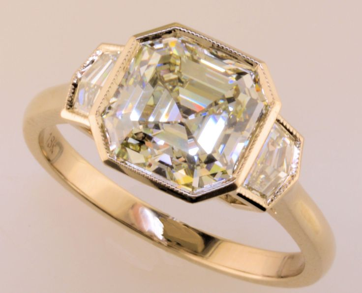 """Look at this unusual engagement ring! A gorgeous Asscher cut diamond is flanked by """"Cadillac cut"""" diamonds and set in raw white gold."""