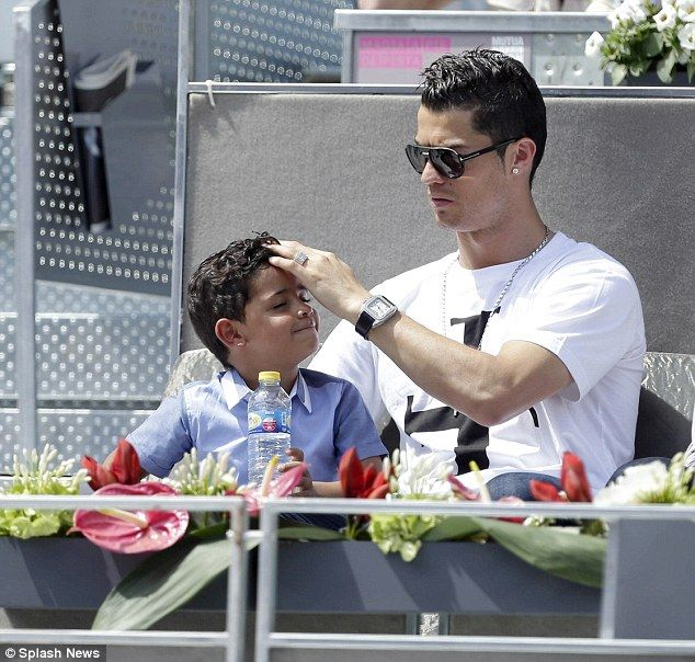 Fussing: Ronaldo messed with his son's hair after opting for a casual white T-Shirt and je...