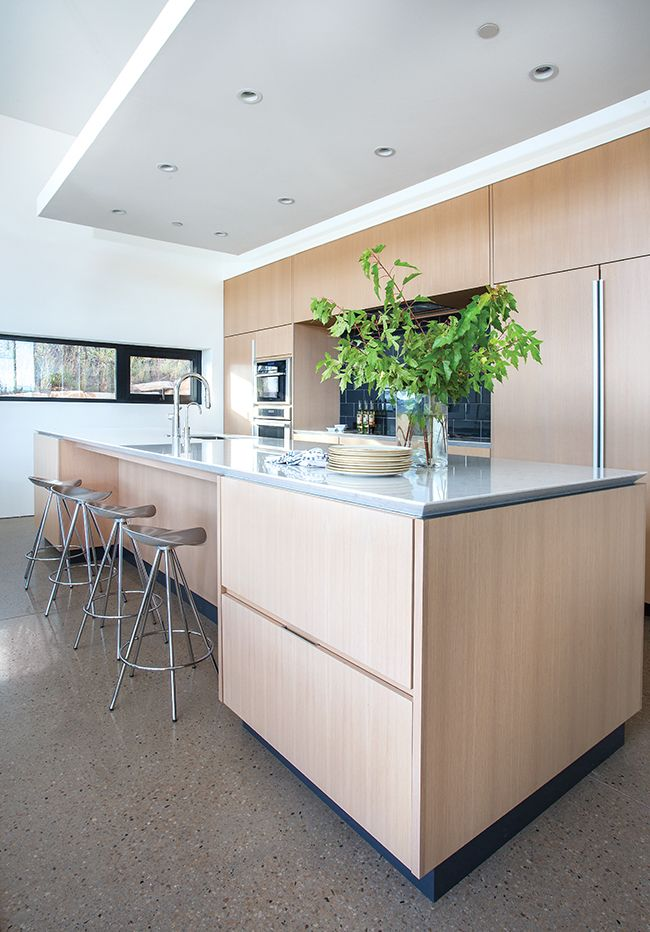 White oak kitchen cabinets feature hidden door pulls and distinct kerf lines. The quartz counter's knife-edge detail makes the surface appear to slightly float above the base cabinets. The floor's polished concrete with aggregate adds contemporary flair.