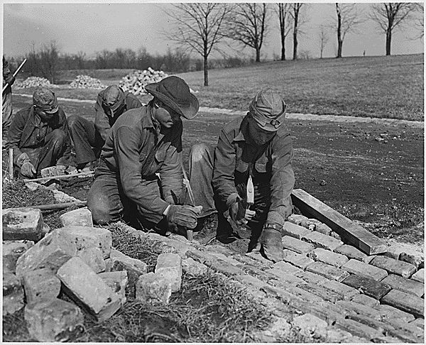 CCC workers constructing road, 1933. Over 3 million unemployed young men were taken out of the cities and placed into 2600+ work camps managed by the CCC.[