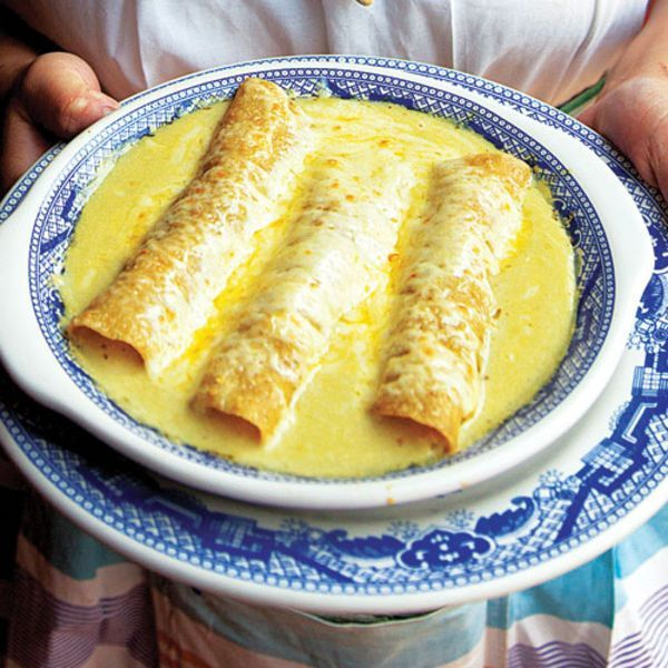 """This cheesy, creamy dish originated at a Sanborns cafe in Mexico City in 1950. Its name, """"Swiss enchiladas,"""" alludes to its copious use of dairy."""