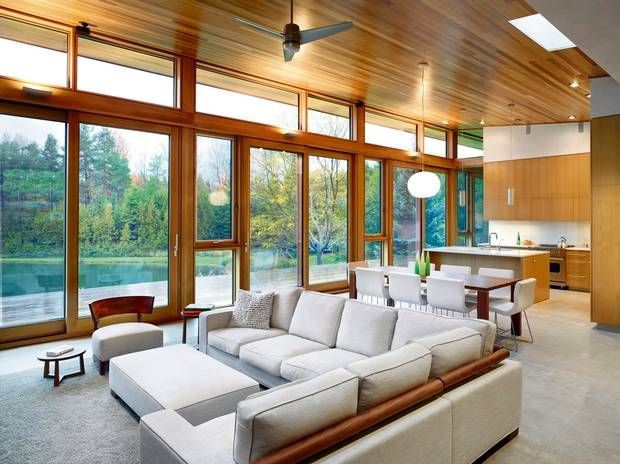 Triple-glazed windows, along with a geothermal heating system that uses the adjacent pond to exchange heat, are among the many features that enable this getaway to tread lightly on the land that surrounds it. (Shai Gil)