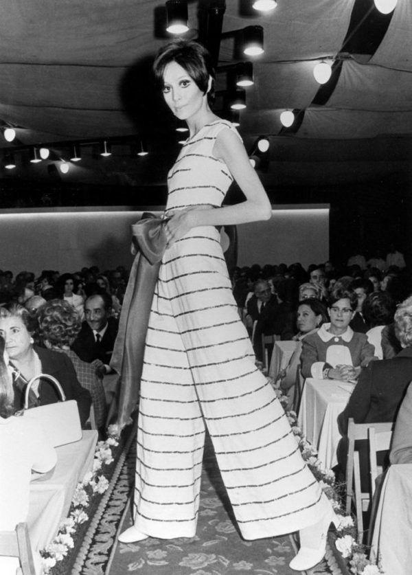 """XIV SEMANA DEL ALGODÓN: Barcelona, 25-5-1969.- Con motivo de la semana del algodón, que hoy finaliza, se celebró un desfile de modelos. Una maniquí presenta una creación consistente en un mono de pantalón, con corte """"moderno"""", de fondo blanco y rayas rojas; en la cintura un gran lazo rosa. EFE/aa"""