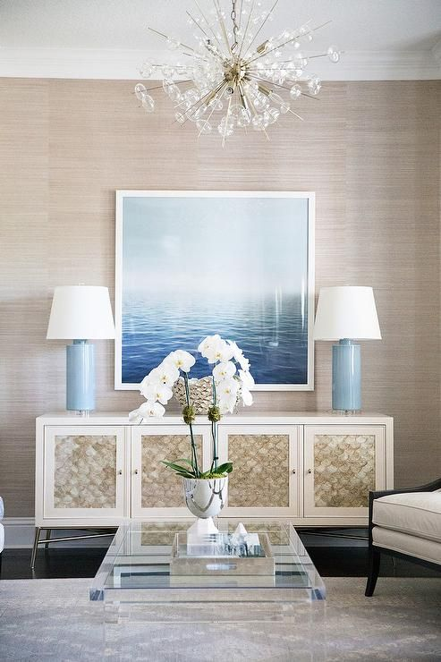 A Solaria Bubbles Chandelier illuminates a living room fitted with a square lucite coffee table placed on a gray rug in front of an Bernhardt Salon Buffet Cabinet.