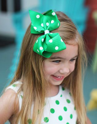 Our polka dot over sized hair bows measure approximately 5-6 inches in width.  These bows include an alligator clip to securely attach to her hair.